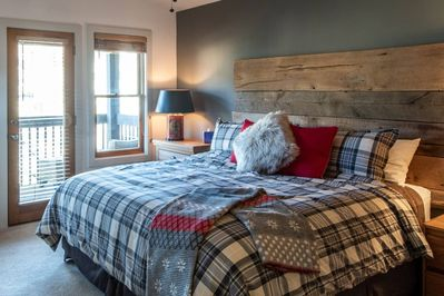 Large master bedroom; king size bed  with private, covered  deck. Views of the ski hill included.
