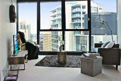 Lounge with leather rocking chair and views across the city to South Bank