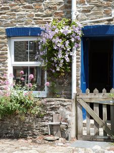 Cottage Entrance with split opening 'barn' door and early flowering clematis