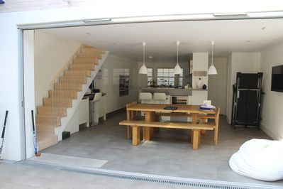 View of basement level with kitchen and dining room when sliding doors are open