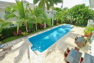 Oversized heated pool and hot tub surrounded by banana trees and coconut palms.
