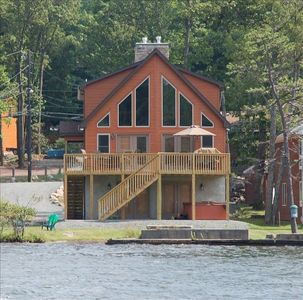 View of house from lake.  Hot tub under deck and grassy lakefront
