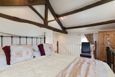 king sized bed in wonderful beamed vaulted ceiling