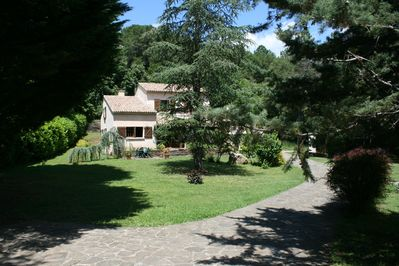 Front of property set in large private gardens and wildlife