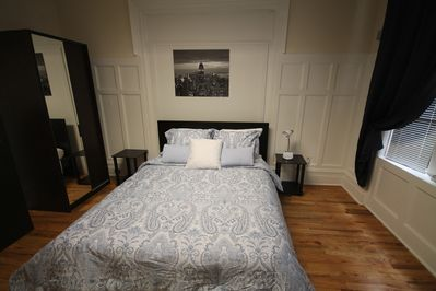 Queen bedroom, bedside tables, window with black out draperies, AC unit