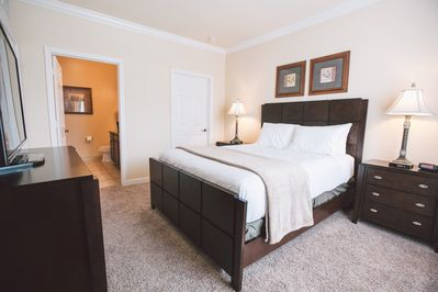 """Master Bedroom with walk in closet and private bath, 42"""" TV on credenza"""