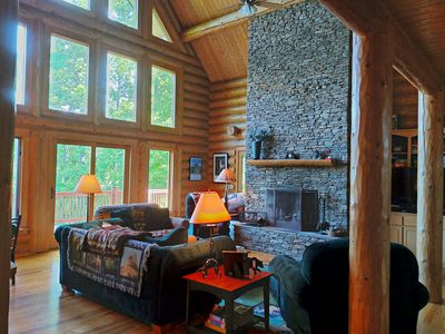 two story great room with stacked stone fireplace and wall of windows for views