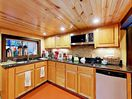 Kitchen  - Wood-paneled ceilings and wood cabinetry lend a rustic air in the kitchen.