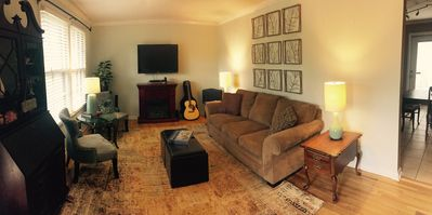 Spacious, cozy living room with acoustic guitar for guest entertainment.