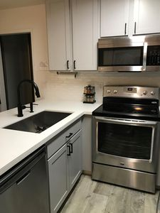 Remodeled kitchen with stainless steel appliances and quartz counters and