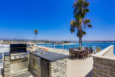 The back porch of this Mission Beach Rental House, complete with grill area and seating,.