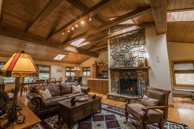 Living room with gas log fireplace, leather furniture and TV