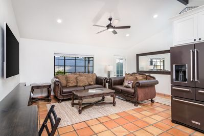 Living Area with Two Sofas, Coffee Table, TV, Desk, Chair, and Refrigerator.