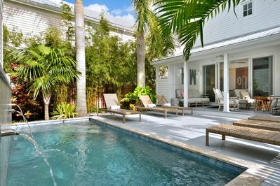 Immaculate outdoor area with heated pool and tranquil waterfall.