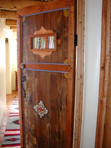 Hand carved interior door separating King or 2 Twins & Queen bedrooms down private hall