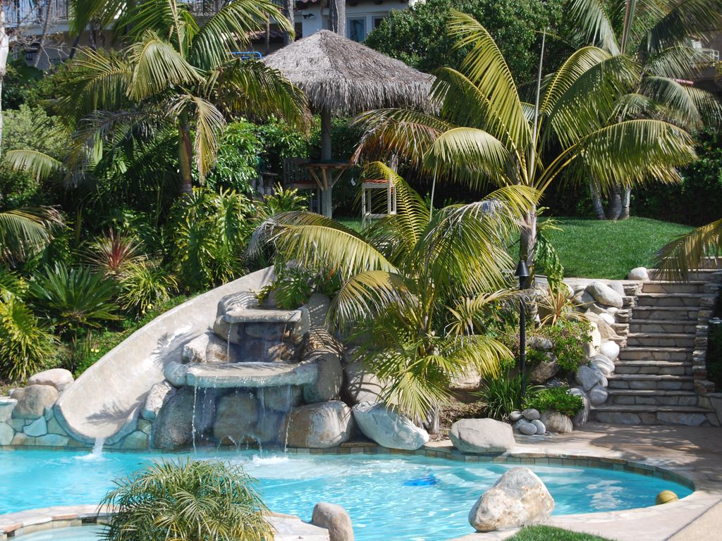 backyard pool slide waterfall and jacuzzi accented with 4 tiki lights - Cool Pools With Waterfalls And Slides