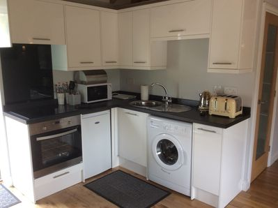 Kitchen - with electric hob, oven, washing machine and ample storage.