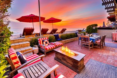 Welcoming beach inspired deck with lots of casual seating, fire pit, and a table for dining al fresco while watching the sun set over the Pacific.