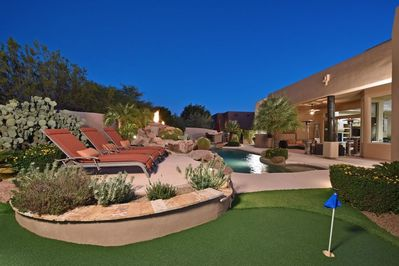 3 hole putting green with 3 sun lounge chairs overlooking the pool