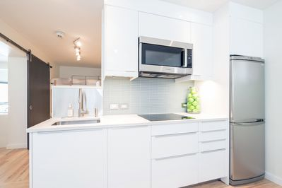 The kitchen has an induction cooktop (please note, no oven), full sized fridge & microwave.