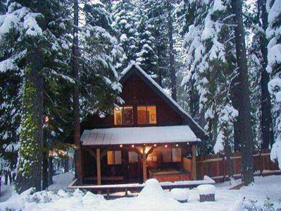 Snowy rear chalet with hot tub and BBQ.