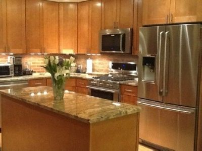 Kitchen with new stainless steel Electrolux appliances and granite  countertops.