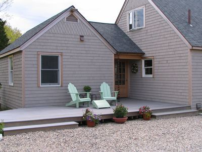 Front of the house with deck and chairs.  Door to entry & the great living area.