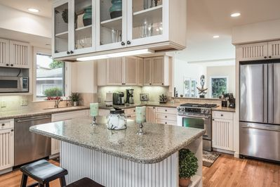 Bright modern family kitchen looks into large family room. Bar seating for 2.