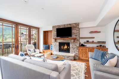 Spacious living area with a gas fireplace, flat screen TV, and deck access to take in the gorgeous mountain views