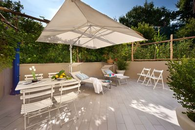 Terrace with dining table and chairs, BBQ, sun beds, garden, shower.