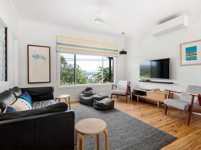 Photo for Seagrass Cottage - Watch the boats and birds float by over Brisbane Waters from the brand new front deck, or cook up a BBQ feast on the spacious, private rear patio with its own mesmerising view of the backyard escarpment up to Bouddi National Park.