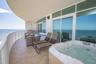 A balcony with a hot tub, 2 lounge chairs, 4 chairs, and an outdoor sofa & grill