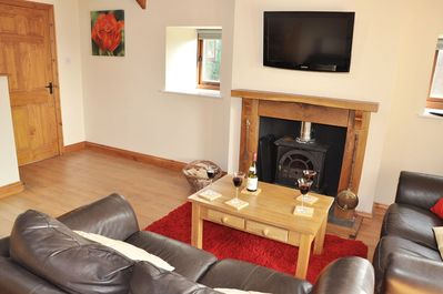 Ground floor: Spacious open plan sitting room with a wood burning stove