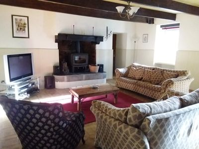 Living room with comfortable seating for six and wood burner