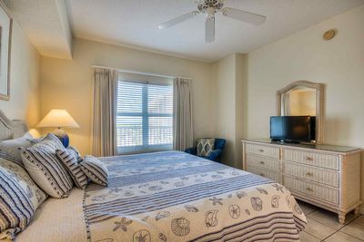 Sunny master bedroom has room darkening curtains so you can sleep in if you want