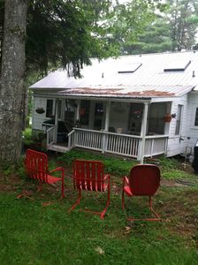 There are plenty of chairs, a covered porch with a table and chairs and benches