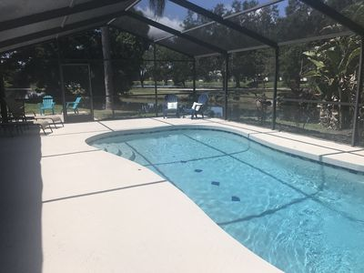 Outdoor pool area with paver outside, lounge chairs and covered patio, screen