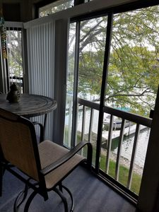 Balcony with table and two chairs. Stair access to dock