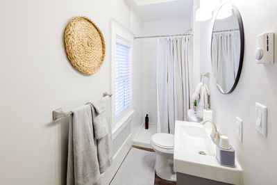 Light and bright washroom with standup shower and fresh linens.