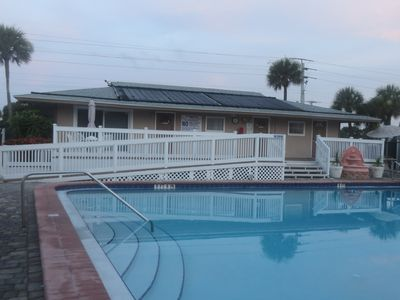 Condo clubhouse with bathrooms, plenty of chairs & tables for relaxing poolside!