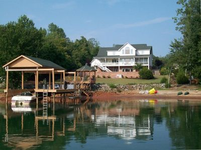 A view of the home from the lake. A private cove with a dock, gazebo and toys.