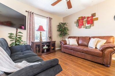 Lovely living room with leather couch, loveseat & futon. Couch is a pullout so