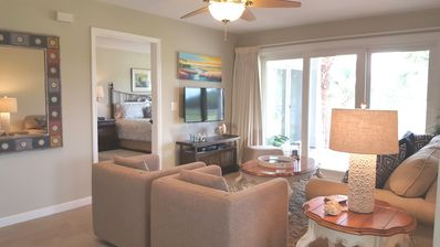Living room seen from dining room with partial view of master bedroom. Tilt wall mounted TV.