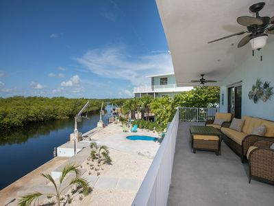 Photo for Private canal front home with pool and ocean access.