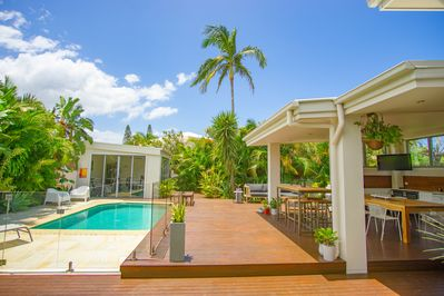 Covered alfresco dining area with outdoor kitchen overlooks the pool and gym
