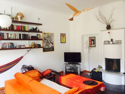 the living room with a hammock, openfire, books and a bird to watch over you