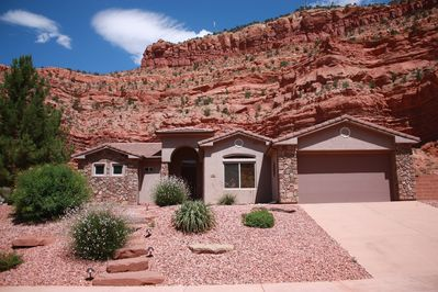 House backs up to stunning cliffs, and faces more red mountains across canyon.