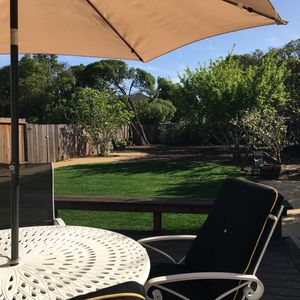 One of two shade umbrellas in expansive private yard.