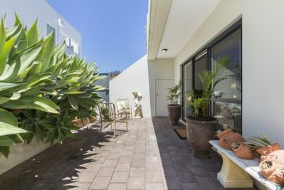 Sunny rear courtyard with clothesline and outdoor setting