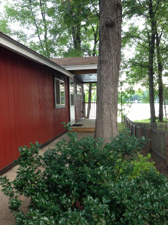Front door of red cottage with covered porch and view of lake. 2 cottages on Whalen lake  Baldwin MI      HomeAway Baldwin